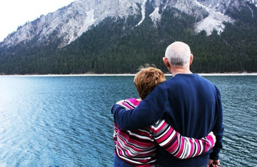 Photo of older couple looking out over water and mountain.